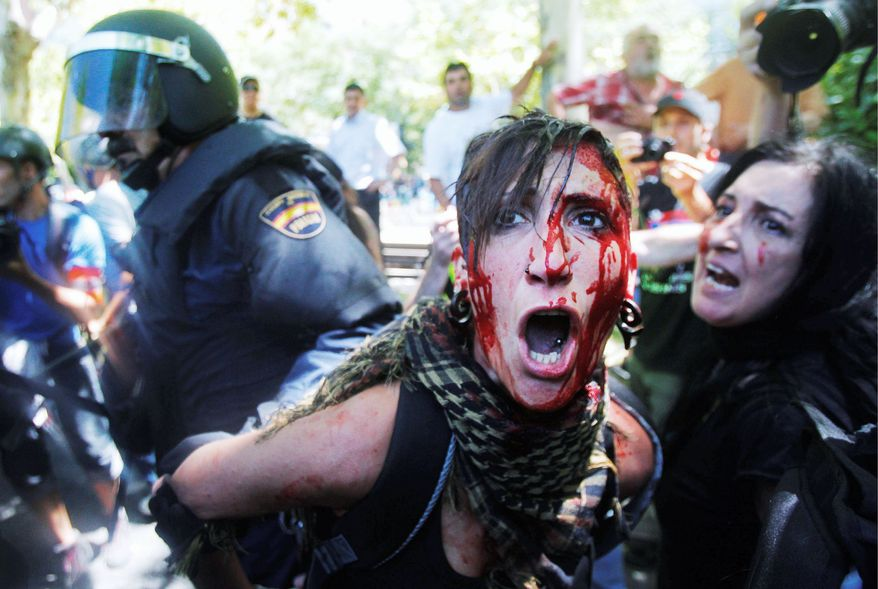A demonstrator bleeds as she is detained by riot police during a protest march by miners to the Minister of Industry building in Madrid on Wednesday. Angered by huge cuts in subsidies, the miners converged on the capital for protest rallies after walking nearly three weeks from the mines. (Associated Press)