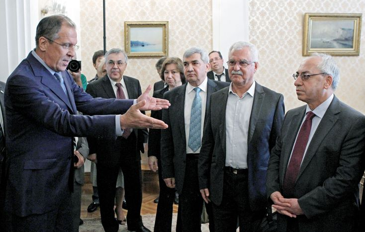 """Russian Foreign Minister Sergey Lavrov (left) welcomes a delegation headed by Abdulbaset Sieda (right), a leader of the Syrian National Council (SNC), in Moscow, on Wednesday. Afterward, Mr. Sieda said he saw """"no change"""" in Moscow's stance. (Associa"""