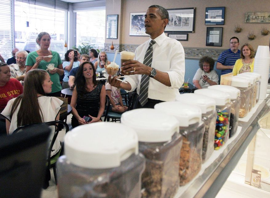 President Barack Obama brings ice cream to members of his staff during a stop at Deb's Ice Cream and Deli in downtown Cedar Rapids, Iowa, before heading to the airport on Tuesday, July 10 2012. (AP Photo/The Gazette, Cliff Jette)