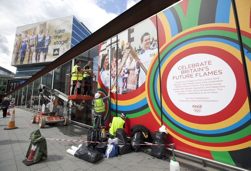 Workers put up advertising at a shopping mall near the London 2012 Olympic Park on July 11, 2012, as work continues to ready the site for the Summer Games, which begin July 27. (Associated Press)
