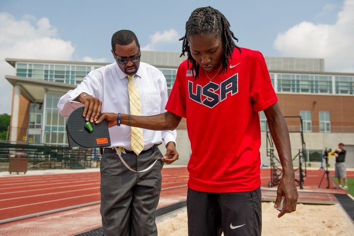 Olympic long-jumper Brittney Reese measures her distance to the sand with her coach Mark Pryor, left, while training at Coppin State University, Baltimore, Md., Friday, May 25, 2012. (Andrew Harnik/The Washington Times)