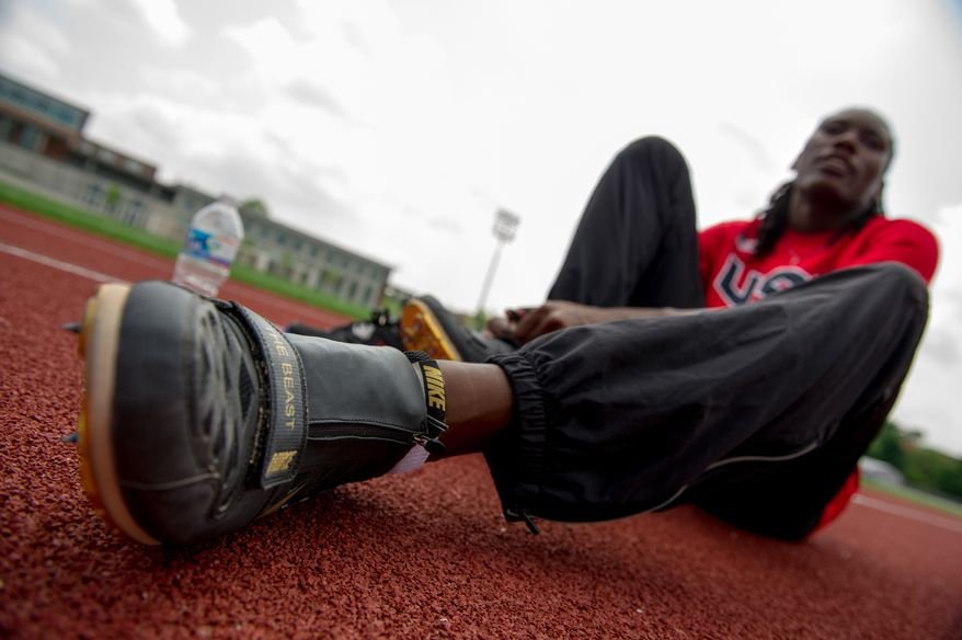 "Olympic long-jumper Brittney Reese ties her custom Nike shoes which has her nickname ""The Beast"" written on one shoe as she trains at Coppin State University, Baltimore, Md., Friday, May 25, 2012. (Andrew Harnik/The Washington Times)"