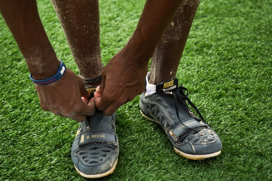 """Olympic long-jumper Brittney Reese ties her custom Nike shoes which has her nickname """"The Beast"""" written on one shoe as she trains at Coppin State University, Baltimore, Md., Friday, May 25, 2012. (Andrew Harnik/The Washington Times)"""