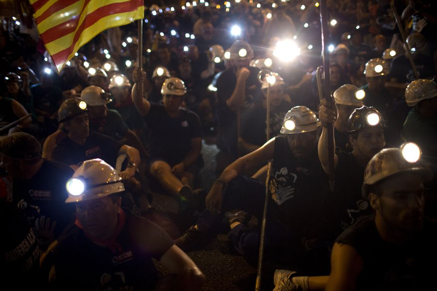 Protesting miners rest during a march after walking for more than 20 days from the northern Asturias and Leon regions on their way to the Puerta del Sol plaza in Madrid on Tuesday, July 10, 2012. (AP Photo/Emilio Morenatti)