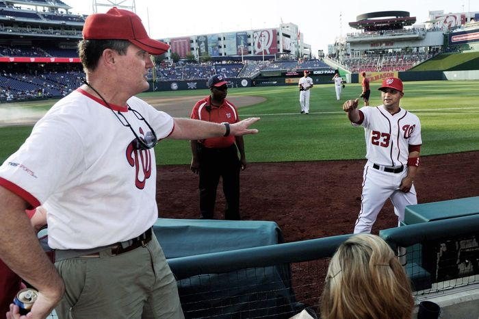 """Steve Wilson catches up with Nationals catcher Jhonatan Solano, one of the players who has stayed with the Wilsons, before a game at Nationals Park. Phyllis Wilson (below) says, """"They do mean a lot to you."""" This year, the family was unable to host players because their daughter gave birth to their first grandchild. Above right, a collection of mementos decorates the Wilsons' basement. (Preston Keres/Special to The Washington Times)"""