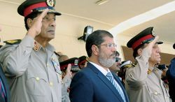 Egyptian President Mohammed Morsi (center) is flanked by Field Marshal Hussein Tantawi (left) and Chief of Staff Sami Anan at a ceremony at an Air Force base in Cairo on Tuesday. U.S. Secretary of State Hillary Rodham Clinton arrives in the Egyptian capital on Saturday amid growing concern in Washington that a power struggle in Egypt could imperil the transition to democratic rule. (Associated Press)