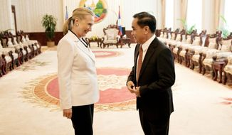 Hillary Rodham Clinton speaks with Laotian Prime Minister Thongsing Thammavong Wednesday during her historic visit to Laos, the first by a U.S. secretary of state since 1955. She also visited a Buddhist temple and viewed artificial limbs at a center that provides free prosthetics to Laotians wounded by bombs left over from the Vietnam War. (Associated Press)