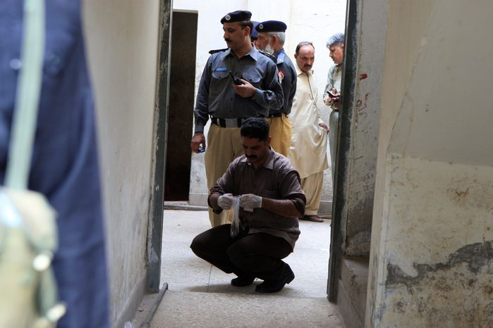 Pakistani investigators gather evidence at a house attacked by gunmen in Lahore, Pakistan, on Thursday. Taliban gunmen also opened fire on a compound housing policemen, killing nine of them, officials said. (Associated Press)