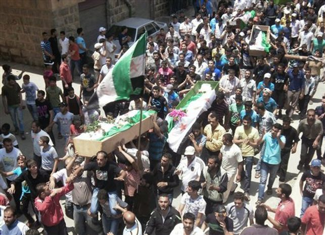 This citizen journalism image provided by Shaam News Network SNN, purports to show anti-Syrian regime mourners carrying the coffins of Syrian citizens wrapped with Syrian revolutionary flags who were killed by the Syrian forces shelling, in Daraa, southern Syria, Tuesday June 26, 2012.