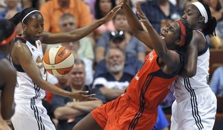 ** FILE ** Washington Mystics' Crystal Langhorne, center, falls into Connecticut Sun's Tina Charles, right, after losing the ball as Sun's Allison Hightower watches during the first half of a WNBA basketball game in Uncasville, Conn., Wednesday, July 11, 2012. (AP Photo/Jessica Hill)