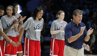 United States Olympic women's basketball coach Geno Auriemma, right, applauds with Seimone Augustus, left, Maya Moore, and Lindsay Whalen during a practice Saturday, July 14, 2012 in Washington. (AP Photo/Alex Brandon)