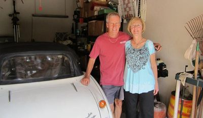 Robert Russell and his wife, whose name was not given, are shown in their Texas garage with Mr. Russell's prized 1967 Austin Healy sports car, which was stolen 42 years ago and recovered recently after he spotted it on eBay, authorities said on Sunday, July 15, 2012. (AP Photo/Los Angeles County Sheriff's Department)