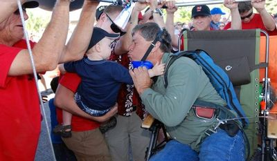 Lawn chair balloonist Kent Couch leans in for a kiss from a grandson before taking flight from his gas station with Iraqi adventurer Fareed Lafta on Saturday, July 14, 2012 in Bend, Ore. (AP Photo/Jeff Barnard)
