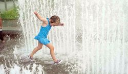 Annabel Helms, 4, from the District, cools off in the water fountain at The Yards Park on Monday. The area is experiencing another surge of steamy weather. (Raymond Thompson/The Washington Times)