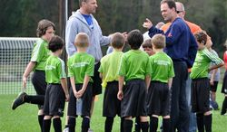 This Oct. 1, 2011 photo shows coaches Jeff Goldman, left, and Jack Russell with their team, the Sounders, at the Raynham Soccer complex in Raynham, Mass. Both Goldman and Russell have sons on the team. Parents who sign up to coach appreciate the experience because it's usually fun and builds dedicated time with their kids into their schedule. Often, they're also trying to ensure that their kids learn proper techniques and good sportsmanship. (AP Photo/Carolyn Lessard)