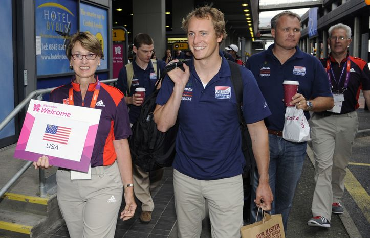 Members of the U.S. Olympic sailing team are escorted following their arrival at Heathrow Airport in London, Monday, July 16, 2012. Heathrow is set to welcome a record number of passengers Monday as athletes begin arriving for the London Olympics. (AP Photo)