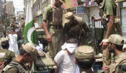 Pakistani soldiers escort an alleged suspect arrested during a crackdown operation against militants in Bannu, Pakistan, on Monday, July 16, 2012. (AP Photo/Ijaz Mohammed)
