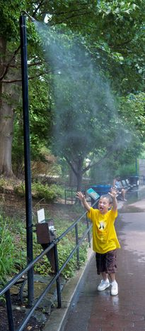 Michael Sweeney, 6, of Gulfport, Fla., cools off at the National Zoo on a day when local temperatures reached the triple digits. The push-button misters help the zoo save water. (Barbara L. Salisbury/The Washington Times)