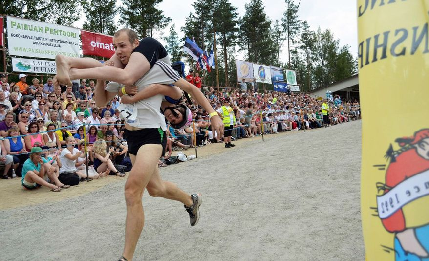 In the wife-carrying world championships, held in Sonkajarvi, Finland, men carry women on their shoulders while climbing over obstacles and crossing a pool of water. (Veera Tegelberg/Special to The Washington Times)