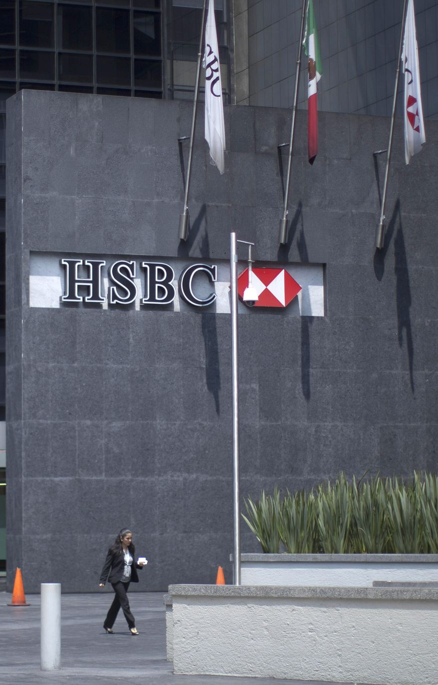 A woman walks in front of the HSBC bank headquarters in Mexico City, Tuesday, July 17, 2012. The chief compliance officer of Britain's HSBC Tuesday said he was stepping down from that position after an investigation found that lax controls at the international bank allowed Mexican drug cartels to launder billions of dollars through its U.S. operation and other illicit transactions. (AP Photo/Alexandre Meneghini)