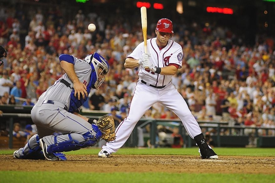 Mets' catcher Josh Thole fails to control a wild pitch from Pedro Beato (not pictured) while Tyler Moore bats in the bottom of the tenth inning during the Washington Nationals game against the New York Mets at Nationals Park, Washington D.C.,Tuesday, July 17, 2012.   The wild pitch allowed Ryan Zimmerman to score from third base to win the game for the Nationals 5-4.  (Ryan M.L. Young/The Washington Times)