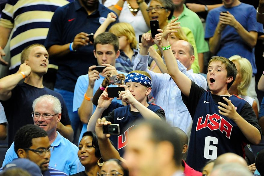 Fans take pictures of President Obama as he arrives during an exhibition game July 16, 2012, between the U.S. men's basketball team and Brazil at Verizon Center in D.C. (Ryan M.L. Young/The Washington Times)