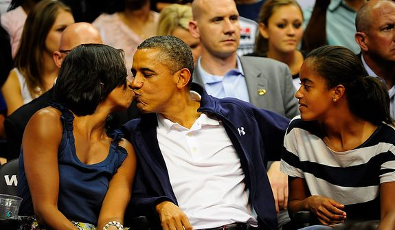 President Obama kisses first lady Michelle as they and daughter Malia (right) take in an exhibition game July 16, 2012, between the U.S. men's basketball team and Brazil at Verizon Center in D.C. (Ryan M.L. Young/The Washington Times)