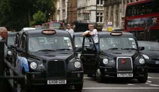 London taxi drivers park their cabs on the junction of Whitehall and Parliament Square, as they take part in a protest to jam traffic in reaction to not being allowed to use the Olympic driving lanes in London, Tuesday, July 17, 2012. (AP Photo/Matt Dunham)