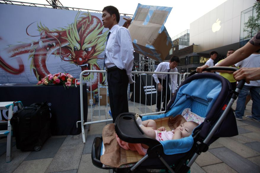 A baby rests in a pram near the site of an event to support Chinese athletes going to the Olympics in Beijing Tuesday, July 17, 2012. (AP Photo/Ng Han Guan)