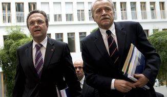 German Interior Minister Hans-Peter Friedrich, left, and outgoing head of the domestic intelligence agency Heinz Fromm arrive at a press conference in Berlin, Wednesday July 18, 2012. Germany faces a growing threat from militant Islamists and far-right fringe groups, including small extremist cells and lone wolf operators, top security official said Wednesday. (AP Photo/dapd/Michael Gottschalk)