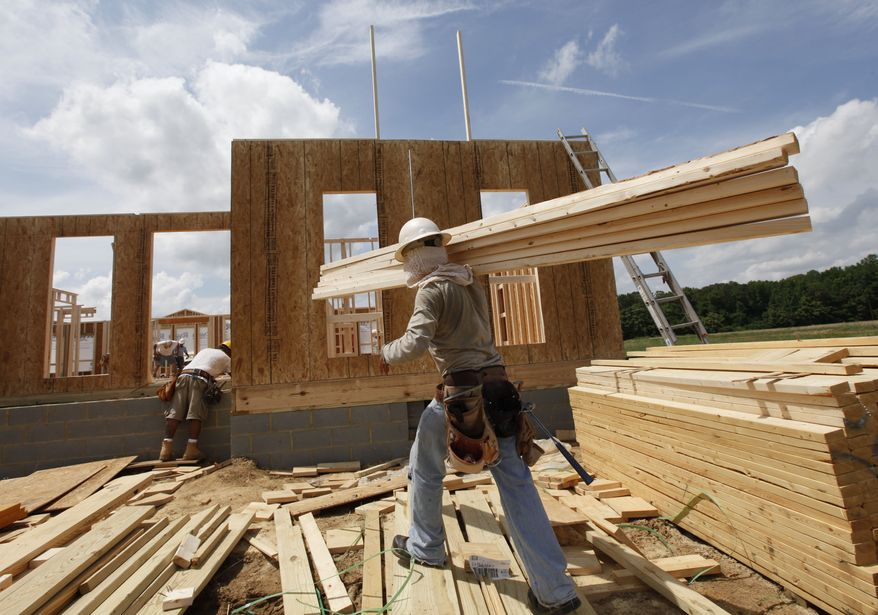 **FILE** A construction worker carries a load of wood to a new home as they frame the house in Chester, Va., on May 16, 2012. (Associated Press)