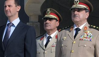 Syrian President Bashar Assad (left) stands next to Gen. Dawoud Rajha (right), Syria's defense minister, during a ceremony to mark the 38th anniversary of the October 1973 Arab-Israeli war, in Damascus, Syria, on Thursday, Oct. 6, 2011. (AP Photo/SANA)