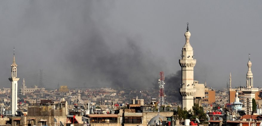 In this citizen journalist image, smoke billows over Damascus, Syria, on July 18, 2012, after a bomb ripped through a high-level security meeting. Three top regime officials, including President Bashar Assad's brother-in-law, were killed in the blast. (Associated Press)