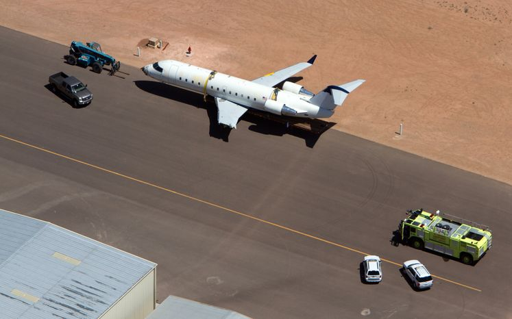 A SkyWest regional jet sits on the tarmac on the opposite end of the St. George Municipal Airport Tuesday, July 17, 2012. A SkyWest Airlines employee wanted in a murder case attempted to steal a passenger plane, then shot himself in the head after crashing the aircraft in a nearby parking lot, officials said Tuesday. Brian Hedglin, 40, scaled a razor wire fence at the St. George Munici