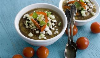 This gazpacho soup is prepared with grilled summer vegetables and topped with tangy feta cheese and balsamic vinegar. (Associated Press)