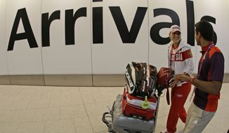 Russian tennis player Elena Vesnina talks with an Olympic volunteer after arriving at Heathrow Airport outside London on Wednesday, July 18, 2012, as the city prepares for the 2012 Summer Olympics. (AP Photo/Charlie Riedel)
