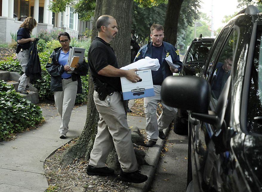 FBI agents load a box of materials into an SUV outside Trenton, N.J., Mayor Tony Mack's house on July 18, 2012, following a middle-of-the-night raid. Mack's two-year administration of New Jersey's impoverished capital city has been marked by accusations of nepotism and reckless spending. Mack, 46, emerging later in the morning from his home, denied any wrongdoing. (Associated Press/The Trentonian)