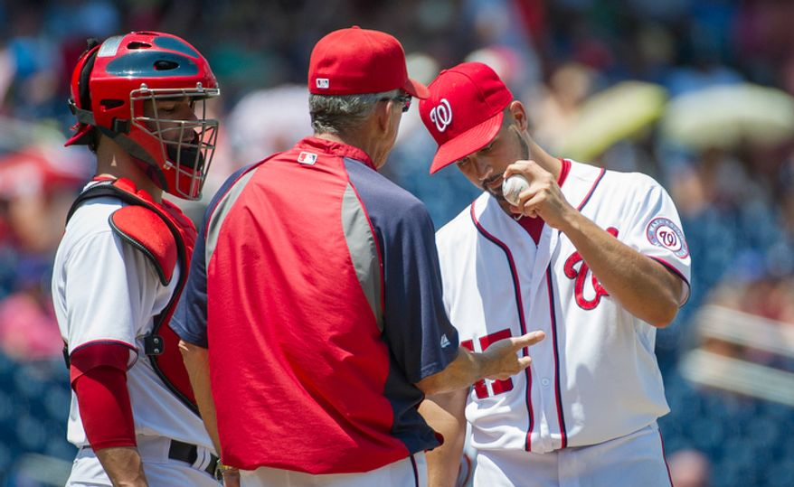 Gio Gonzalez hands the ball over manager Davey Johnson as he is relieved in the top of the fourth inning. (Rod Lamkey Jr./The Washington Times)