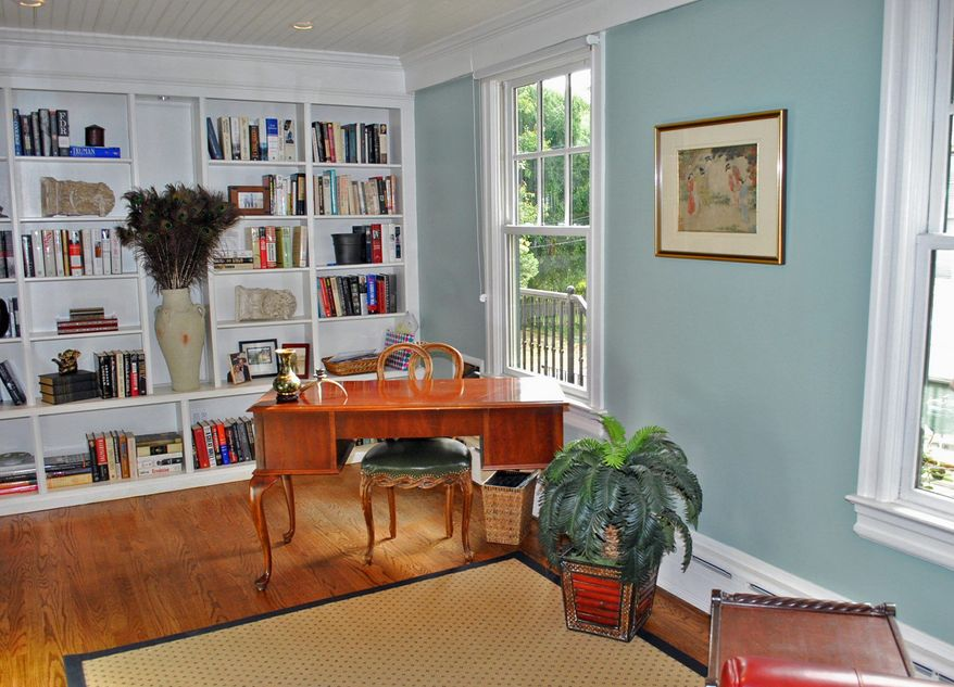 The library has two walls of built-in bookcases, large windows, hardwood flooring and a beadboard ceiling.