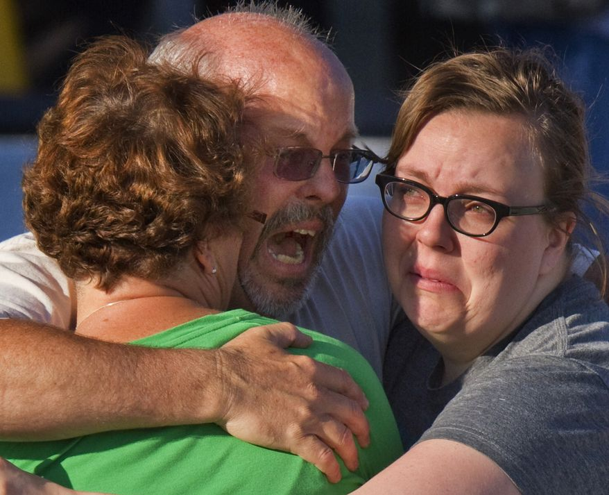 "Tom Sullivan (center) embraces family members July 20, 2012, outside Gateway High School in Aurora, Colo., where witness were brought for questioning after a gunman opened fire in a crowded movie theater, killing 12 people and injuring at least 50 others. Sullivan was frantically searching for his son, Alex, who was celebrating his 27th birthday by going to see ""The Dark Knight Rises,"" the movie where the gunman opened fire. (Associated Press)"