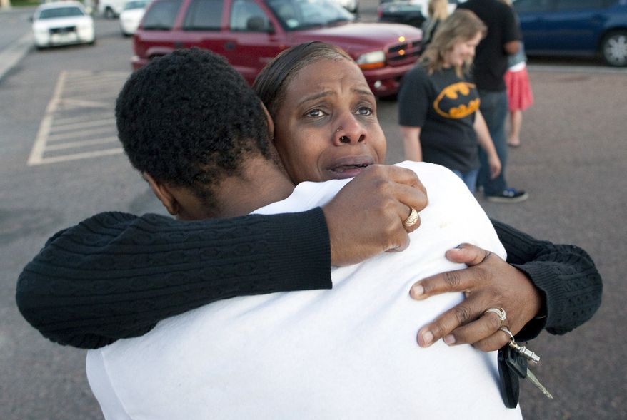 "Shamecca Davis hugs her son, Isaiah Bow, outside Gateway High School in Aurora, Colo., where witness were brought for questioning after a gunman opened fire in a crowded movie theater, killing 12 people and injuring at least 50 others. Bow, who was an eyewitness, left the theater during the shooting but went back in to find his girlfriend. ""I didn't want to leave her in there. But she's OK now,"" Bow said. (Associated Press)"