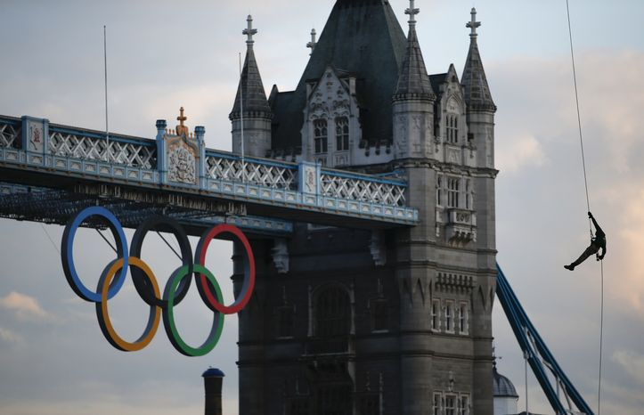 British Royal Marine Martyn Williams, right, rappels down from a Royal Navy Sea King helicopter into the Tower of London with the Olympic torch, Friday, July 20, 2012, in London. The Olympic Torch arrived in London after