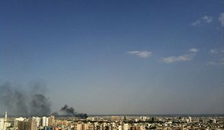 **FILE** Smoke rises over the skyline July 19, 2012, in the Qaboun neighborhood of Damascus, Syria, during shelling by Syrian government forces. (Associated Press)