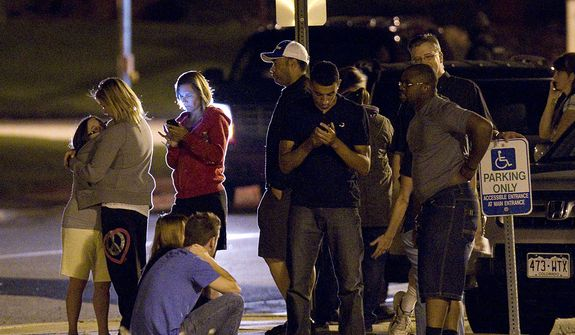 People use mobile devices July 20, 2012, as they wait outside Gateway High School in Aurora, Colo., where witness were brought for questioning after a gunman opened fire in a crowded movie theater, killing 12 people and injuring at least 50 others. (Associated Press)