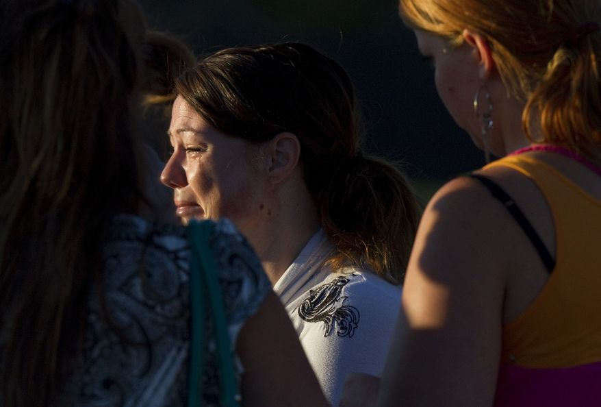A woman cries July 20, 2012, outside Gateway High School in Aurora, Colo., where witness were brought for questioning after a gunman opened fire in a crowded movie theater, killing 12 people and injuring at least 50 others. (Associated Press)