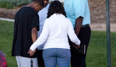A small group prays July 20, 2012, outside Gateway High School in Aurora, Colo., where witness were brought for questioning in regard to a gunman's rampage at a movie theater that left 12 dead and at least 50 others injured. (Associated Press)