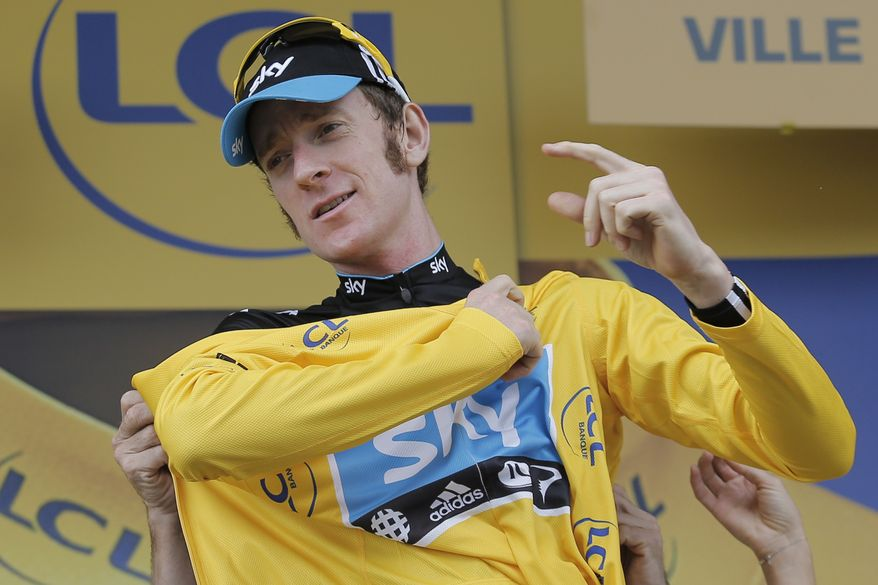 Bradley Wiggins of Britain puts on the overall leader's yellow jersey on the podium of the 18th stage of the Tour de France cycling race over 222.5 kilometers (138.3 miles) with start in Blagnac and finish in Brive-la-Gaillarde, France, Friday July 20, 2012. (AP Photo/Christophe Ena)