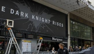 "Workers in Paris dismantle July 20, 2012, an installation setup for the premiere of ""The Dark Knight Rises,"" which was scheduled to be held that night but was canceled after a gunman killed 12 people at a Colorado opening of the same film earlier in the day. (Associated Pres)"