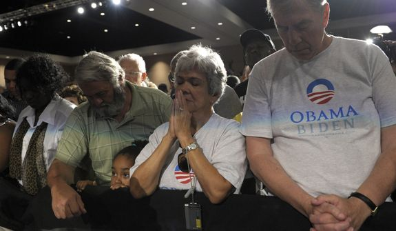 People observe a moment of silence July 20, 2012, at an event at the Harborside Event Center in Ft. Myers, Fla., with President Obama for the victims of the Aurora, Colo., shooting. Obama, who was scheduled to spend the day campaigning in Florida, cancelled his campaign events to return to Washington to monitor the shooting. (Associated Press)