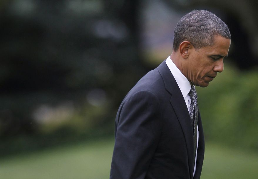 President Obama walks July 20, 2012, across the South Lawn of the White House in Washington following his arrival on the Marine One helicopter. Obama cut short his campaign stop in Florida in the aftermath of the tragic mass shooting at a movie theater in Aurora, Colo. (Associated Press)